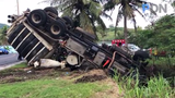 The driver and a passenger are transported to the hospital after  a wastewater tanker truck overturns just before entering the village of Umatac on Oct. 5, 2019.