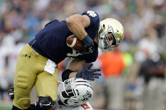 Notre Dame tight end Cole Kmet (84) scores a touchdown against Bowling Green defensive back Jamari Bozeman (13) during the first half of an NCAA college football game, Saturday, Oct. 5, 2019, in South Bend, Ind. (AP Photo/Darron Cummings)