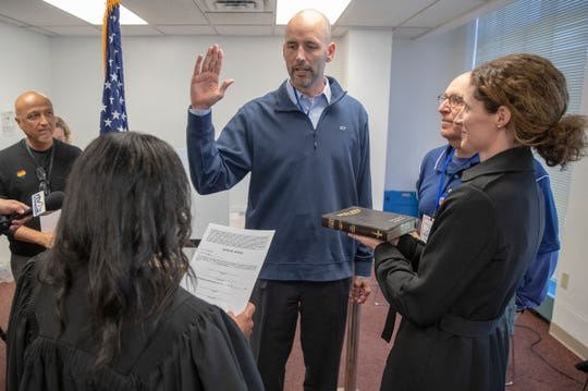 Ryan Mears, newly elected Marion County Prosecutor, flanked by his wife Shannon Mears, right, and former prosecutor Terry Curry, is sworn in Saturday by Circuit Court Judge Cheryl Lynch. Mears beat Mayor Hogsett's pick, Tim Moriarty.