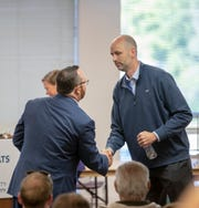 Ryan Mears, right, shakes the hand of his opponent, Tim Moriarty, after winning the role of Marion County Prosecutor in Indianapolis on Saturday, Oct. 5, 2019.