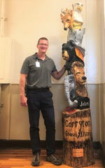 "Corryton Elementary School principal Aaron Maddox with the new 8-foot totem pole created by Jeff Banning, of Wood Carved Creations, on Oct. 3. ""We originally thought about putting it outside,"" Maddox said. ""We wanted it to last forever, and in the lobby it is the first thing you see. It's a focal point and tells the story of our Corryton family – six houses, one family also carved into the pole as well."""