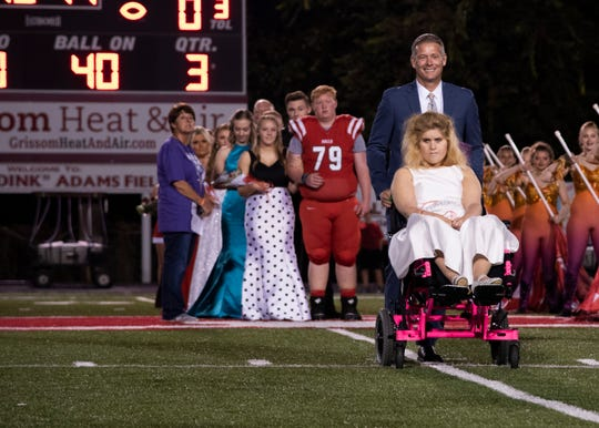 Halls homecoming court member Blakeley Irwin is escorted to the field during the Halls vs. Central game on Friday, Oct. 4, 2019.