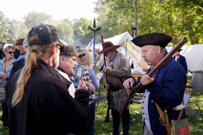 Brad Belcher of Danville, Ind. answers questions about his Kentucky Rifle after a demonstration during the 52nd Feast of the Hunters' Moon, Saturday, Oct. 5, 2019, at Fort Ouiatenon in West Lafayette. Belcher first came to the Feast in 1977 as a student and Purdue University and hasn't missed one since.
