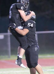 Plymouth's Logan Walkley (6) celebrates one of his three touchdowns with lineman Sean Britt (54) in a 35-13 victory over Hartland on Friday, Oct. 4, 2019.