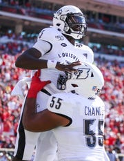 Louisville's Micale Cunningham gets lifted by Caleb Chandler after scoring the Cards' first TD against Boston College Saturday afternoon at Cardinal Stadium. Oct. 5, 2019