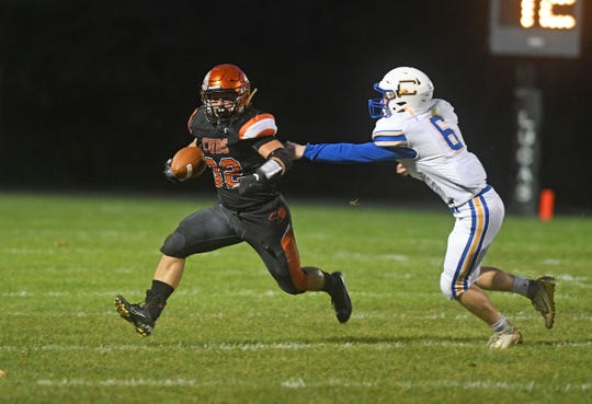 Cubs running back Tommy Zirzow tries to elude Steubenville Catholic Central's Nick Kissinger during their game Friday night at Lucas High School.