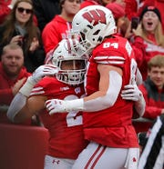 Running back Jonathan Taylor celebrates one of his touchdowns against Kent State with UW teammate Jake Ferguson.