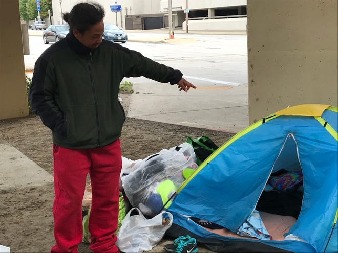 Antwon Harrison points to the tent he lives in at the downtown Milwaukee homeless encampment known as Tent City. Harrison and other occupants of the camp have been ordered by the state Department of Transportation to leave the property beneath the Interstate 794 overpass by Oct. 31.