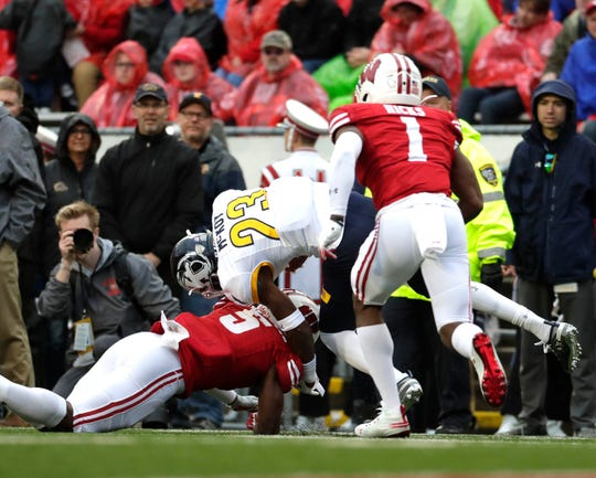 UW cornerback Rachad Wildgoose takes down Kent State wide receiver Isaiah McKoy after a gain of just 2 yards as the Badgers' Faion Hicks closes in.