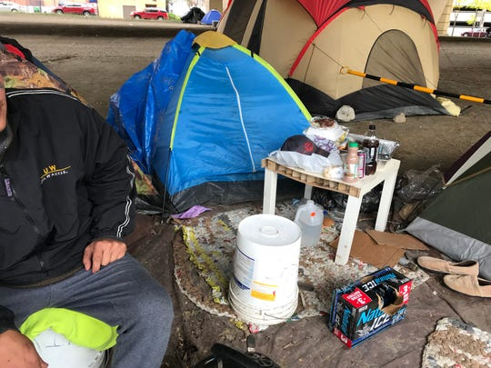 A man named Brian sits outside the tent he lives in Saturday at the downtown Milwaukee homeless encampment known as Tent City. Occupants of the camp have been ordered by the state Department of Transportation to leave the property beneath the Interstate 794 overpass by Oct. 31.