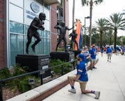 Florida fans pay tribute to the Tim Tebow statue at Ben Hill Griffin Stadium in Gainesville, Fla.., on Saturday, Oct. 5, 2019.