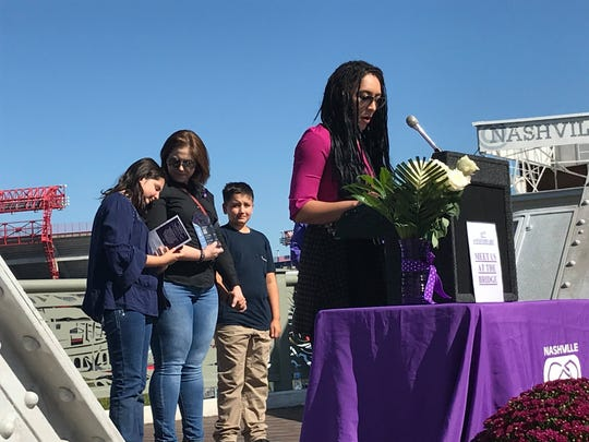 Mikayla Lewis, an award-winning journalist and domestic violence survivor, addresses the crowd at the Meet Us at the Bridge event on Saturday, Oct. 5, 2019. Behind her, Summer Sabie, also a survivor, stands with her two children on the John Seigenthaler Pedestrian Bridge as victims are remembered.