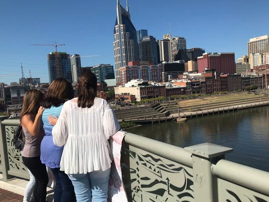 The family of Ashley Yarbrough, a 24-year-old who died as a result of domestic violence, throws a purple rose over the side of the John Seigenthaler Pedestrian Bridge on Oct. 5, 2019. It was part of the Meet Us at the Bridge event to remember domestic violence victims killed in Nashville.