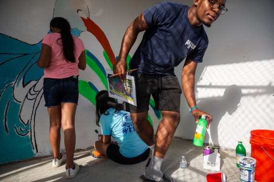 From left to right, Immokalee High School volunteers Saphira Ochoa, 11, Alma Salas, 14, and Wenchy Dutreuil, 16, paint murals on the walls of a highway bridge on Saturday, October 5, 2019, at Village Oaks Elementary School.