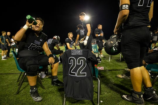 Athletes from Palmetto Ridge High School football team leave a seat for their former teammate Colby Singletary, who passed away in a car crash in July,  during the game against Gulf Coast High School on Friday, October 4, 2019, at Palmetto Ridge High School.