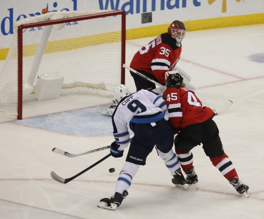 Andrew Copp of the Jets is tied up by Sami Vatanen of the Devils as he comes in on Corey Schneider in the first period.