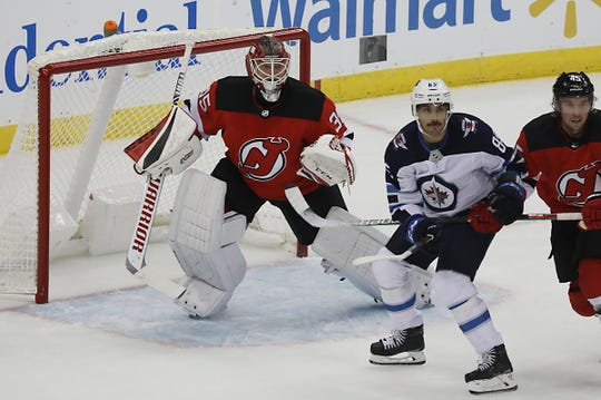 Devil goaltender Corey Schneider looks for the puck as he is partially screened by Mathieu Perreault of the Jets in the first period.