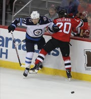 Patrik Laine of the Jets comes together with Blake Coleman of the Devils in the first period.