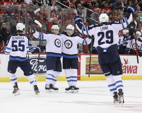 The Jets celebrate a goal by Neal Pionk that tied the game at 4 in the third period.