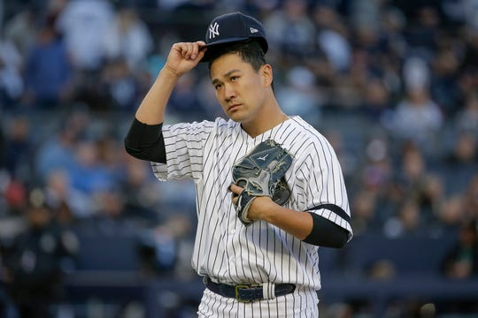 New York Yankees starting pitcher Masahiro Tanaka walks off the field after striking out Minnesota Twins' Miguel Sano to end the top of the second inning of Game 2 of the American League Division Series Saturday, Oct. 5, 2019, in New York.