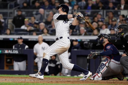 New York Yankees' DJ LeMahieu follows through on a solo home run against the Minnesota Twins during the sixth inning of Game 1 of an American League Division Series Friday, Oct. 4, 2019, in New York.