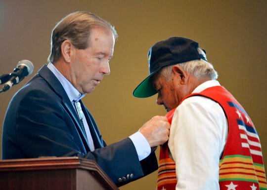 U.S. Sen. Tom Udall, D-New Mexico, left, pins replacement medals to All Pueblo Council of Governors Chairman Edward Paul Torres during a special ceremony at Isleta Pueblo, N.M., Friday, Oct. 4, 2019. Sen. Udall presented the medals to Torres and former Isleta Tribal councilman Diego Lujan, not seen, both veterans of the Vietnam War, after he found out the men were never presented with their earned military medals.