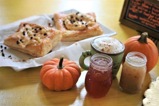In this photo, Nessa Cafe's pumpkin moose Danish, pumpkin pie chai latte, autumn iced tea and a pumpkin pie iced latte sit on a table at the cafe.