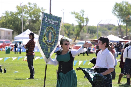 A woman holds the Clan Lamont banner, Saturday, Oct. 5, 2019, during the Aztec Highland Games. Clan Lamont is one of several Scottish clans that were represented at the event.