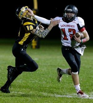 Lourdes quarterback Joshua Bauer (12) stiff-arms Rosholt's Adam Charnecke during a game last month in Rosholt.