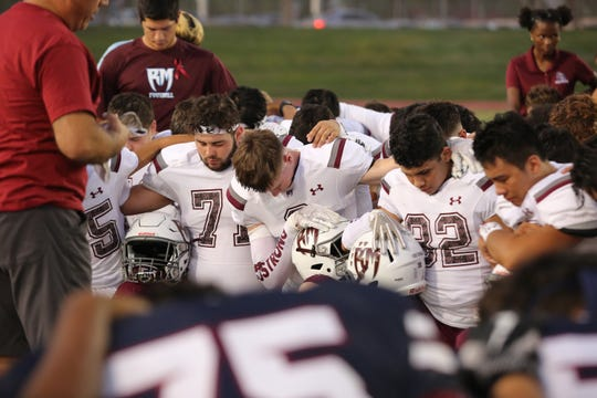 Rancho Mirage and La Quinta football players kneel on the 30-yard line to pray for hospitalized player Israel Ramirez in La Quinta, Calif., on Friday, October 4, 2019.
