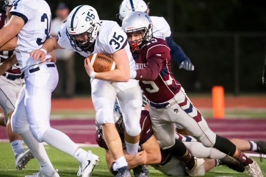 New Oxford's Noah Strausbaugh (15) and Dylan Forbes  tackle Dallastown's Coleton Mahorney (35) during a YAIAA Division I football game on Friday, October 4, 2019.