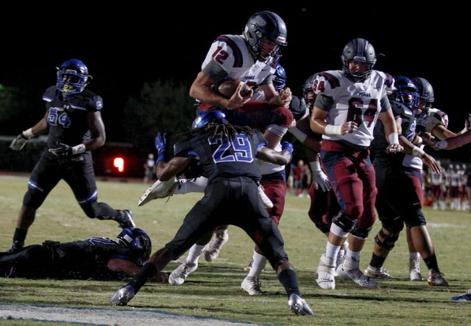 Perry quarterback Chubba Purdy (12) goes airborne over Chandler's defense to score a touchdown during their game in Chandler, Friday, Oct. 04, 2019.