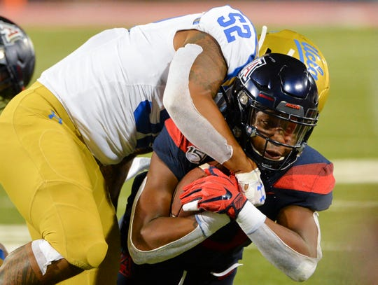 Sep 28, 2019: Arizona Wildcats wide receiver Jamarye Joiner (10) is tackled by UCLA Bruins linebacker Lokeni Toailoa (52) during the second half at Arizona Stadium.