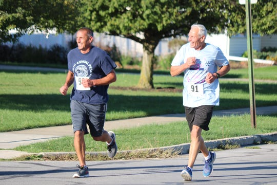 "A pair of runners participating in the annual ""Bras for a Cause"" 5K on Saturday race around town with smiles."