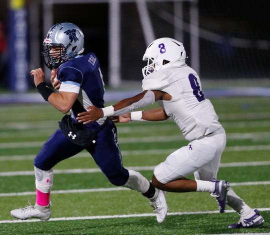 John Jay quarterback Dan Beal attempts to elude a New Rochelle defensive player during their Oct. 4 game.