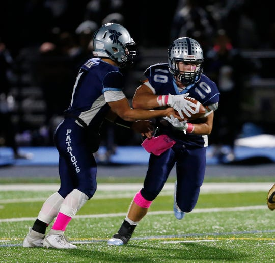 John Jay's Daniel Beal hands off to Luke Mahon during Friday's game versus New Rochelle on October 4, 2019.