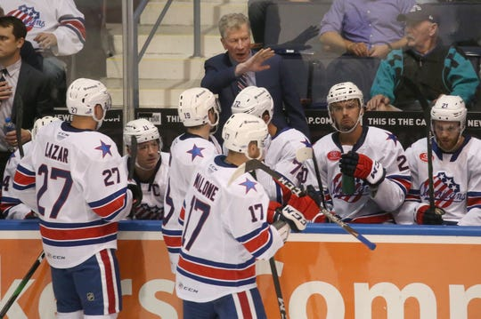 Rochester interim head coach Gord Dineen gives his players instructions from the bench during a TV timeout.