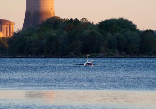 A small plane sits in in a shallow section of the Susquehanna River a few miles from the Three Mile Island nuclear power station after landing on an approach to a Pennsylvania airport,  Friday, Oct. 4, 2019, near Middletown, Pa.