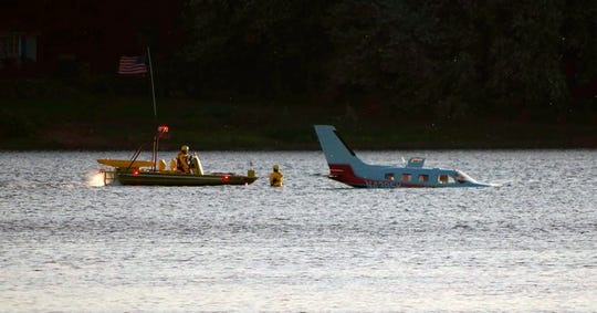 Emergency personnel secure a small plane that landed in in a shallow section of the Susquehanna River a few miles from the Three Mile Island nuclear power station Friday, Oct. 4, 2019, near Middletown, Pa.