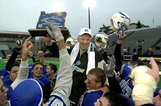 McNary football coach Tom Smythe holds the championship trophy while being carried on the shoulders of his players after the Celtics defeated Sheldon 35-10 in the OSAA 4A championship game on Saturday Dec. 8, 2001.