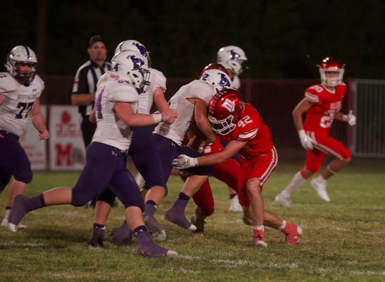 Brayden Dunlap, right, makes a tackle for Miles against Cross Plains on Friday, Oct. 4, 2019.