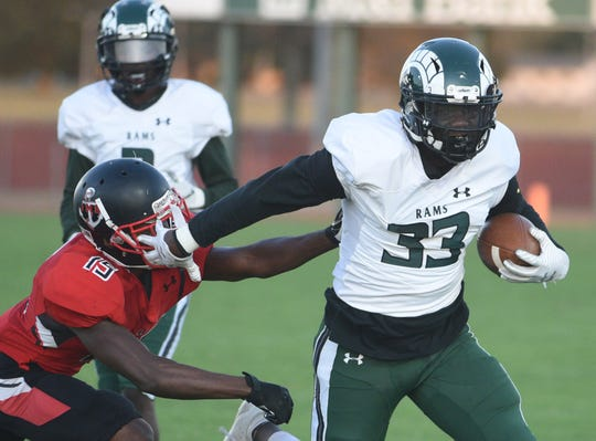 Ram's Jabronte Mills pushes off Bennett's Jordan Mitchell during first half action of Friday's nights game of Parkside High School against James M. Bennett High School at County Stadium. The Rams won the game 28-15. (Photo by Todd Dudek for The Daily Times)