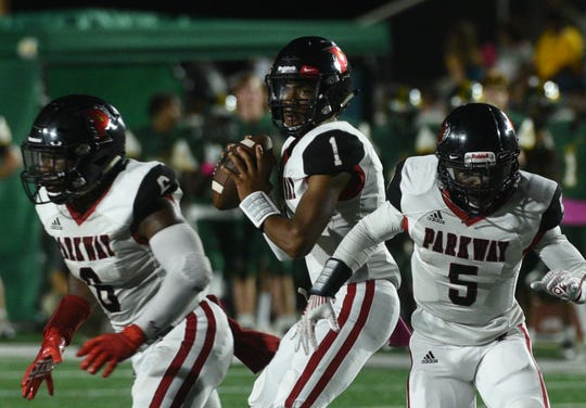Parkway quarterback Gabe Larry prepares to pass while protected by Jamall Asberry (6) and Rontavious Richmond (5).
