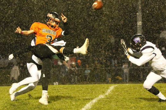 Colin Rentz of Dell Rapids gets off a punt between two Dakota Valley defenders as the rain comes down during Friday's game in Dell Rapids.