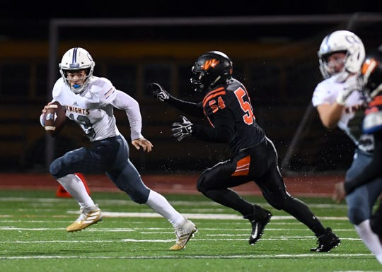 Zach Norton of O'Gorman runs from Ben Bartling of Sioux Falls Washington during their game on Friday, October 4, at Howard Wood Field in Sioux Falls.