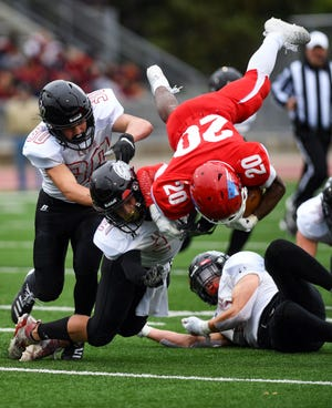 Joe Kolbeck of Brandon Valley knocks Isaiah Robinson of Sioux Falls Lincoln out of the air  during their game on Friday, October 4, at Howard Wood Field in Sioux Falls.