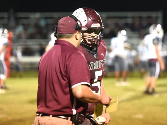 Stuarts Draft's Josh Podgorski talks with quarterback Henry Cooke Friday.