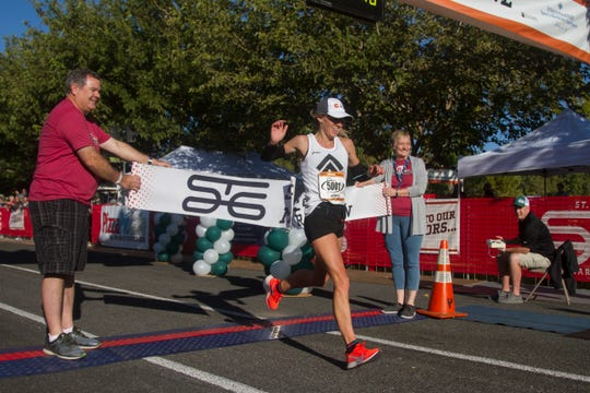 Sylvia Bedford, from South Jordan, is the first female to cross the finish line during the St. George Marathon Saturday, Oct. 5, 2019.