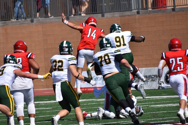 DSU quarterback Keaton Mott hurdles a defender during a game last season.