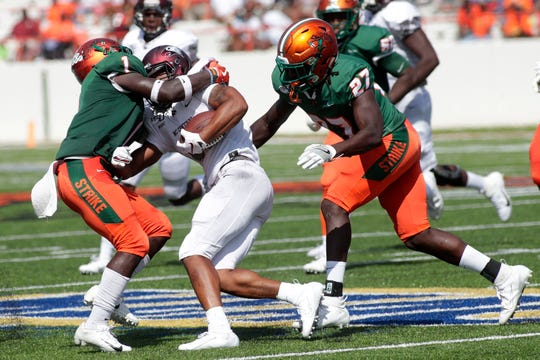 FAMU nickelback Terry Jefferson (left) and linebacker Nadarius Fagan converge to make a tackle against a North Carolina Central player.